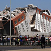 Residents look at a collapsed  building in Concepcion, Chile, Saturday Feb. 27, 2010 after an 8.8-magnitude struck central Chile.(AP Photo)